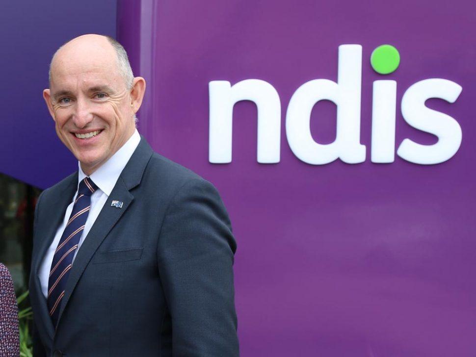 Minister Stuart Robert next to an NDIS sign